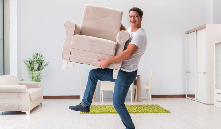 Man arranging furniture in his new home after a house move