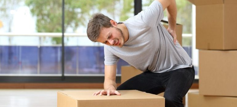 Man with back pain after lifting heavy object