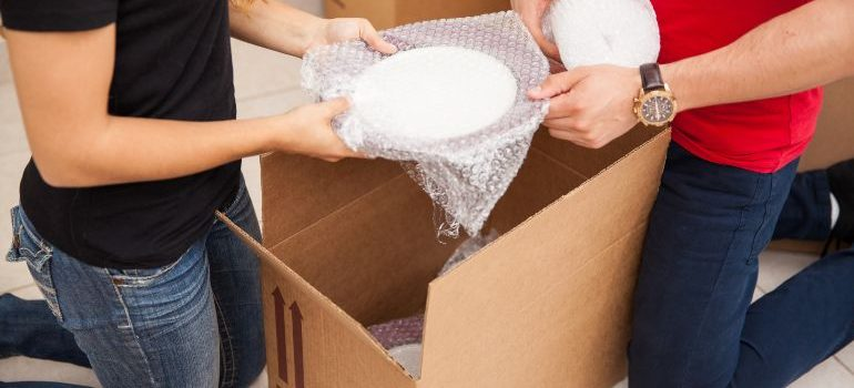 Couple packing fragile items in bubblewrap for moving