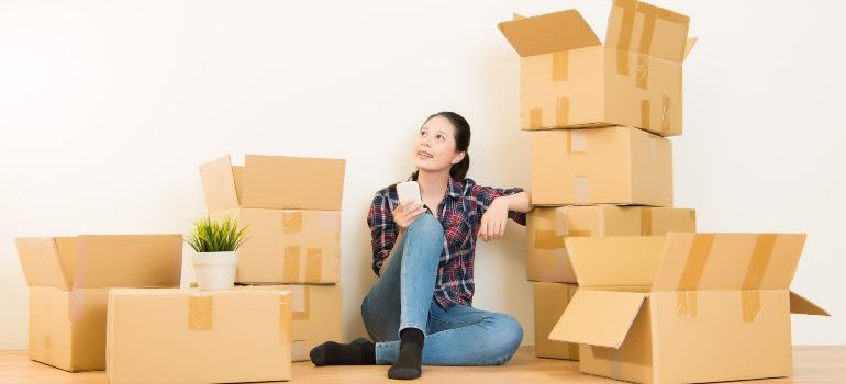 Woman preparing to move house surounded by moving boxes