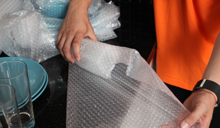 Using bubble wrap to pack glass for moving house