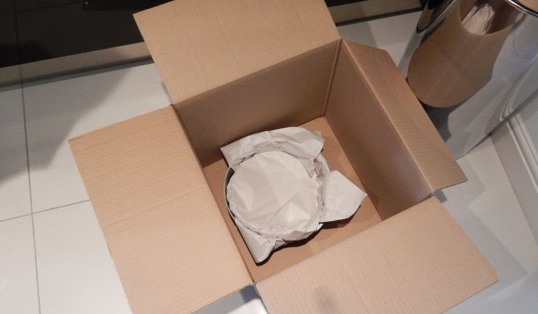 Plates and kitchenware packed in a box ready for a move