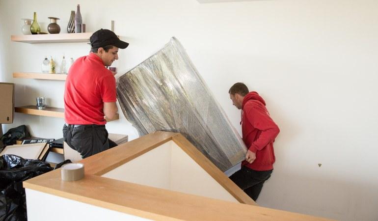 Removals team moving a fridge