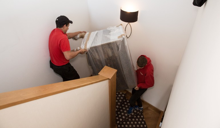 Team moving a fridge down a flight of stairs