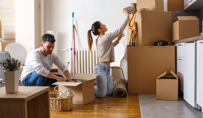 Couple packing moving boxes to move in together