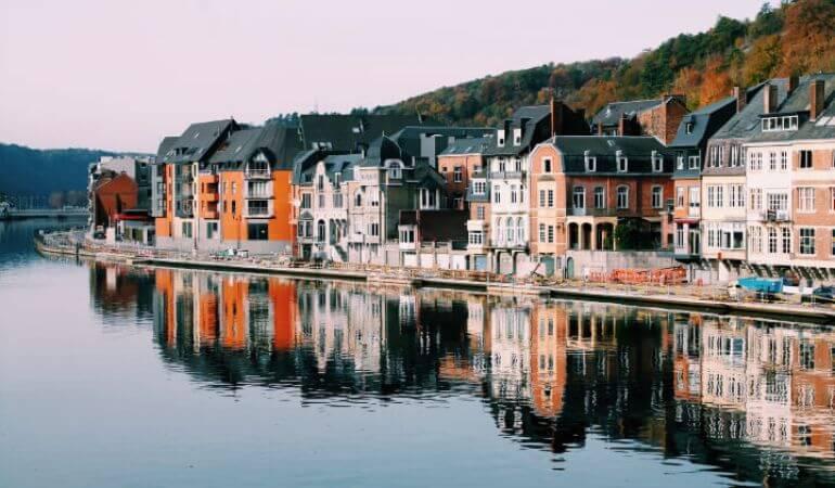 Buldings reflecting in water in Dinant, Belgium