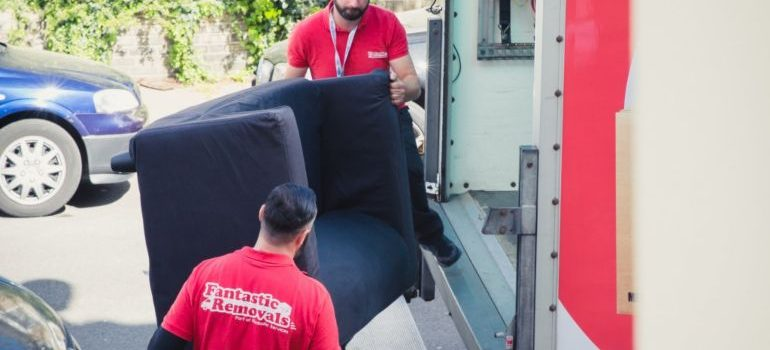 Team of expert movers carying a sofa correctly