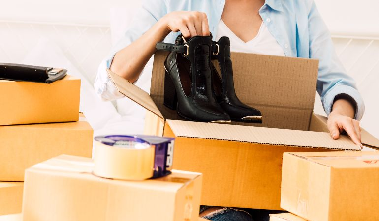 Woman carefully packing her shoes to a move