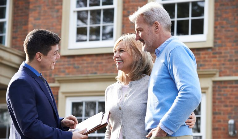Couple making arrangements with their real estate agent for a date to move in