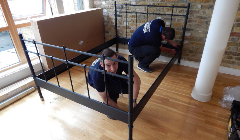 Professional movers dismantling a bed for a move