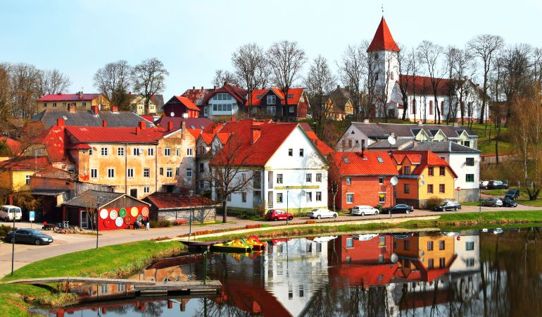 Colorful old town houses and church with lake reflection in spring morning in Talsi Latvia